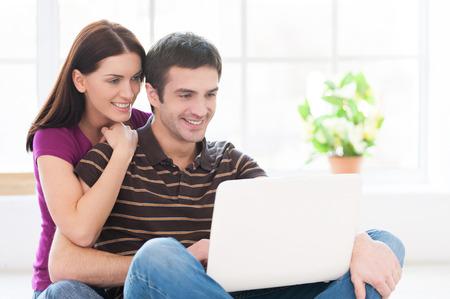 position d amour: Surfer sur Internet est un plaisir. Enthousiaste jeune couple travaillant sur ordinateur portable ensemble, assis sur le sol dans leur appartement