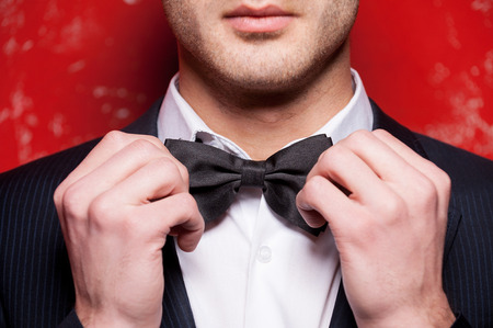 handcarves: Tying his bow tie. Cropped image of handsome young man in formalwear adjusting his bow tie while standing against red background Stock Photo