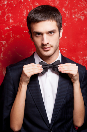 adjusting: Macho in bow tie. Handsome young man in formalwear standing against red background while woman hiding behind him and adjusting his bow tie Stock Photo