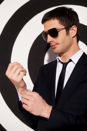 Confident in himself. Handsome young man in formalwear and sunglasses adjusting his shirt cuffs while standing against black and white background Stock Photo - 26313128