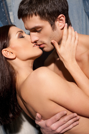 Love and passion. Beautiful young shirtless couple kissing while standing against jeans background Stock Photo