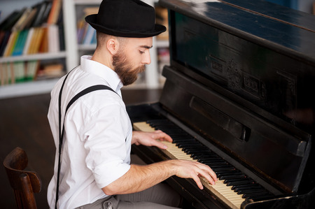 piano: Hacer m�sica. Perfil de un hermoso hombres barbudos j�venes tocando el piano