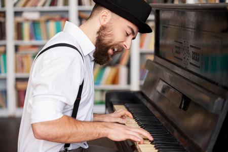 fortepian: Dostał twórczą duszę. Przystojny młody mężczyzna brodaty gry na fortepianie i śpiewu Zdjęcie Seryjne