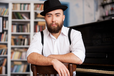 jazz singer: Waiting for inspiration. Portrait of handsome young bearded men sitting in front of his piano