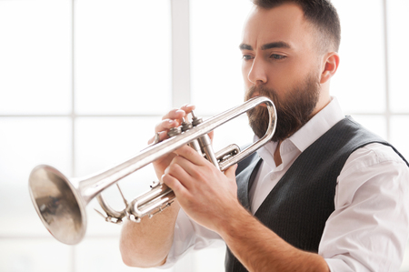 young musician: Improvising with his trumpet. Handsome bearded young men playing trumpet Stock Photo