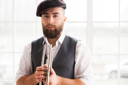 handcarves: Ready for improvising. Handsome young bearded men standing with trumpet in his hands Stock Photo