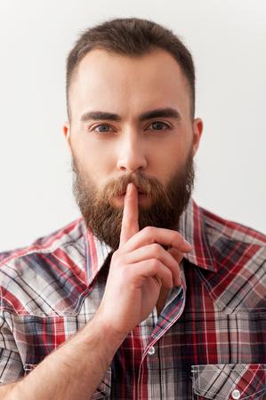 hombre con barba: Guarde silencio. Retrato del hombre barbudo joven y guapo haciendo el signo de la relevancia
