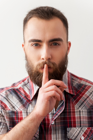 salience: Keep silence. Portrait of handsome young bearded man making salience sign Stock Photo