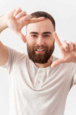 Focusing on you. Handsome young bearded man focusing on you and smiling while standing isolated on grey background photo