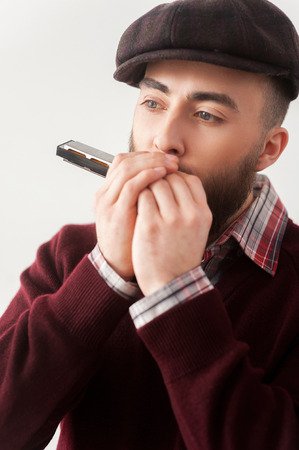 harmonica: Creative soul.  Handsome young bearded men in hat playing harmonica