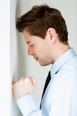 depressed man: Depressed businessman. Side view of depressed young man in shirt and tie leaning at the wall and keeping eyes closed