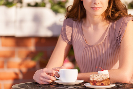 Woman relaxing at the restaurant. Cropped image of attractive young woman drinking coffee at the outdoor cafe photo