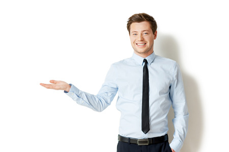Holding copy space. Handsome young man in shirt and tie holding copy space and smiling while standing isolated on white
