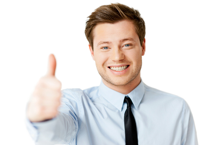Everything is great! Handsome young man in shirt and tie showing his thumb up and smiling while standing isolated on white  photo