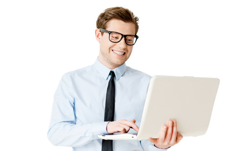IT professional. Handsome young man in shirt and tie working on laptop and smiling while standing isolated on white