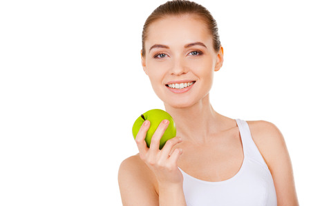 Beauty with green apple. Beautiful young woman holding a green apple and smiling while standing isolated on white photo