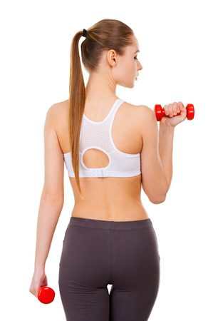 weight loss success: Weight training. Rear view of beautiful young woman in sports clothing training with dumbbells and while standing isolated on white