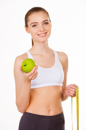 Keeping her body in shape. Beautiful young woman in sports clothing holding apple and measuring tape and smiling while standing isolated on white photo