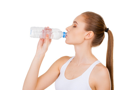 staying: Staying hydrated. Side view beautiful young woman in sports clothing drinking water and keeping eyes closed while standing isolated on white Stock Photo