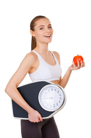 Leaving a healthy life. Side view of beautiful young woman in sports clothing holding weight scales and apple while standing isolated on white photo