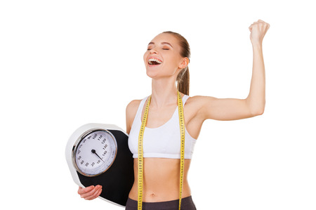 weight scale: Worked off her excess weight. Happy young woman in sports clothing holding weight scale and gesturing while standing isolated on white