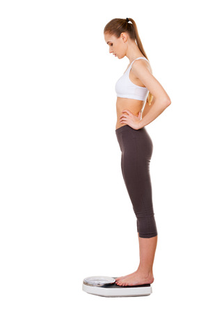 woman on scale: Woman on weight scale. Side view of beautiful young woman in sports clothing standing on weight scale and looking down  Stock Photo