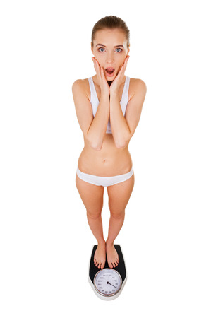 emaciated: Woman with weight scale. Top view of shocked slim woman in underwear standing on weight scale and holding head in hands while isolated on white