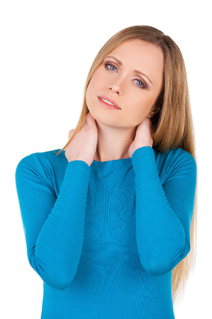 sullen: Feeling pain in a neck. Depressed young woman touching her neck and looking at camera while standing isolated on white Stock Photo