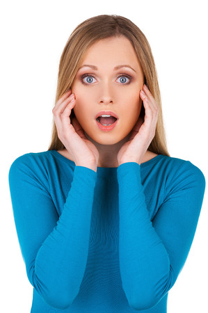 No way! Surprised young woman looking at camera and gesturing while standing isolated on white Stock Photo