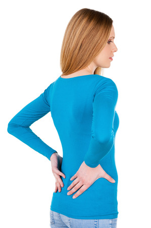 worried woman: Feeling pain in back. Rear view of young woman holding hands on back and looking away while standing isolated on white