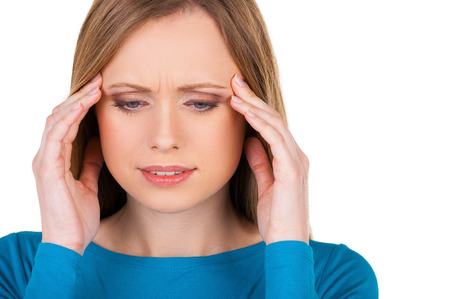 Awful headache. Frustrated young woman touching head with hands and looking down while standing isolated on white photo