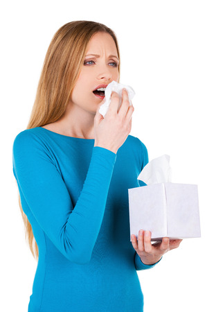 Woman sneezing. Young woman holding handkerchief near face and sneezing while standing isolated on white Stock Photo - 26545173