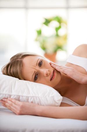dolor de muelas: Mujer que sufre de dolor de muelas. Frustrado joven tocando su mejilla y mirando a la cámara mientras está de pie aislado en blanco Foto de archivo