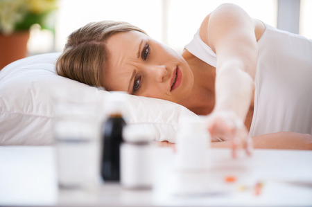 woman lying in bed: I need to take medicines. Young woman stretching out hand and trying to take a bottle with medicines laying on the table