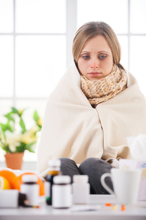 checkered scarf: Sick and hopeless. Young woman covered with plaid looking at the medicines while sitting in bed at her apartment