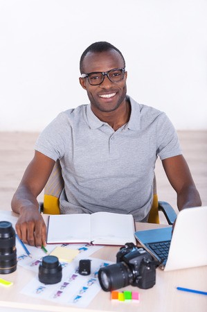 photography themes: Young and creative. Top view of handsome young African man in casual wear sitting at his working place and looking at camera