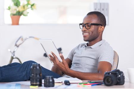 hombres negros: Sentirse seguro y relajado. Hombre africano joven guapo en ropa casual sentado en su lugar de trabajo y de trabajo en la tableta digital