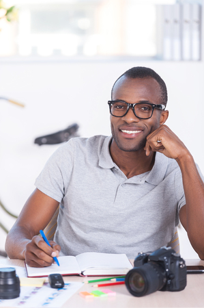 i pad: I love my job! Cheerful young African man in casual wear writing something in note pad and looking at camera while sitting at his working place
