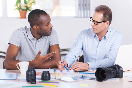 dos personas conversando: Trabajando en proyecto creativo conjunto. Dos hombres de negocios confidentes en ropa casual, sentado junto a la mesa y hablando de algo