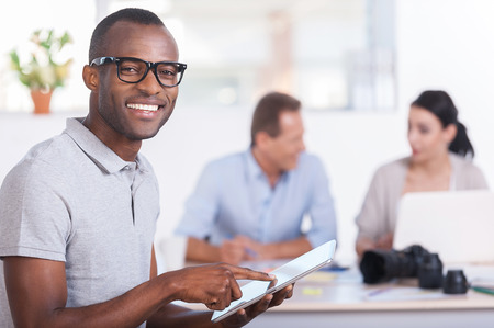 team leader: Cheerful team leader. Handsome young African man working on digital tablet and smiling while two people working on background