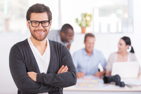 Team leader. Handsome young man in glasses keeping arms crossed and smiling while three people working on background Stock Photo - 26596665