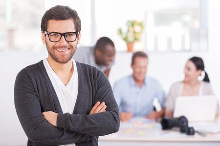 Teamleider. Knappe jonge man in glazen die armen gekruist en glimlachen terwijl drie mensen die werken op de achtergrond