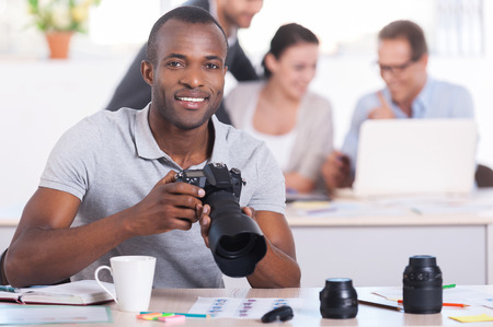 photography themes: Creative people at work. Handsome young African man holding camera and smiling while three people working on background Stock Photo