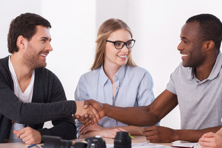photography themes: Friendly handshake. Two business people in casual wear handshaking while woman sitting between them and smiling Stock Photo