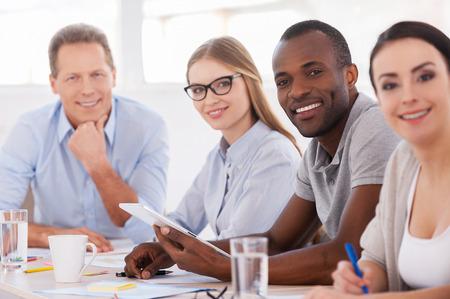강력하고 창조적 인 팀. 비즈니스 사람들이 테이블 주위에 앉아 미소를 카메라의 그룹