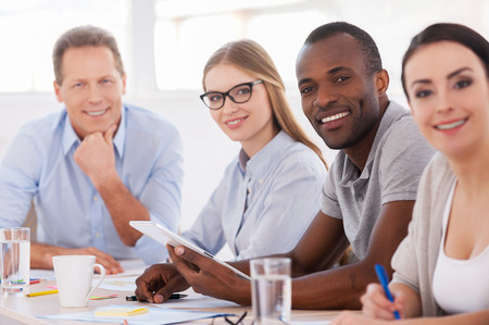 meeting place: Strong and creative team. Group of business people sitting in a row at the table and smiling at camera Stock Photo