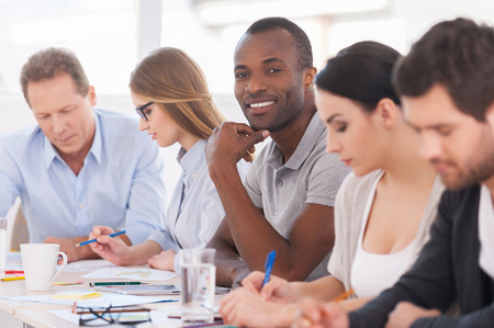 meeting place: I am a part of strong and creative team. Group of business people sitting in a row at the table while handsome African man looking at camera and smiling