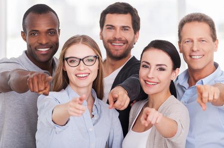 We kiezen voor u! Groep van vrolijke mensen uit het bedrijfsleven in casual wear staan dicht bij elkaar en wijst u