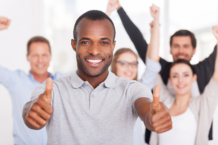 Happy business team. Happy young African man showing his thumbs up you and smiling while group of people in casual wear standing on background photo