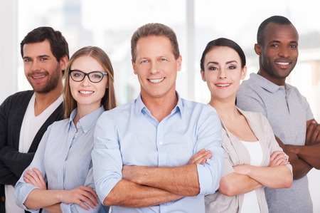 business wear: Confident business team. Group of cheerful business people in casual wear standing close to each other and keeping arms crossed